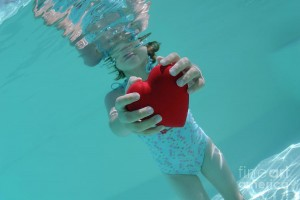 girl-holding-heart-shaped-symbol-in-swimming-pool-sami-sarkis